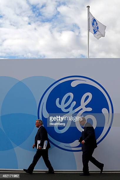 Visitors walk past a GE logo outside the General Electric Co chalet on the first day of the Farnborough International Airshow in Farnborough UK on...