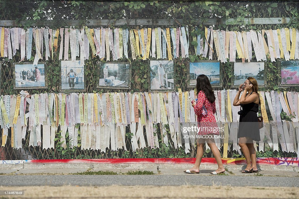 Visitors walk past a giant photograph showing 'Freedom Bridge' at the North-South Korean border, at the 'Wall on Wall' exhibition by German photographer Kai Wiedenhoefer, displayed on a remaining section of the Berlin wall July 26, 2013. Wiedenhoefer's 'Wall on Wall' project features giant panoramic photographs of walls taken in Northern Ireland, Iraq, Cyprus, the West Bank, Morocco, South Korea and the border between the United States and Mexico. The exhibition takes place between10 July and 13 September 2013.