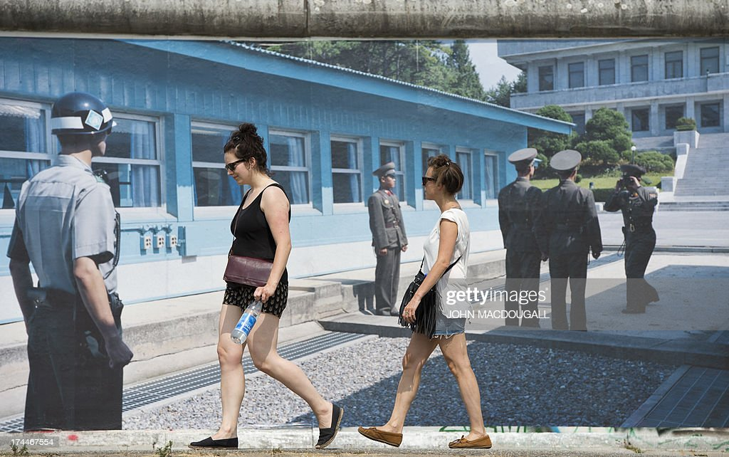 Visitors walk past a giant photograph showing the Demilitarized Zone at Panmunjom (North-South Korea) at the 'Wall on Wall' exhibition by German photographer Kai Wiedenhoefer, displayed on a remaining section of the Berlin wall July 26, 2013. Wiedenhoefer's 'Wall on Wall' project features giant panoramic photographs of walls taken in Northern Ireland, Iraq, Cyprus, the West Bank, Morocco, South Korea and the border between the United States and Mexico. The exhibition takes place between10 July and 13 September 2013.