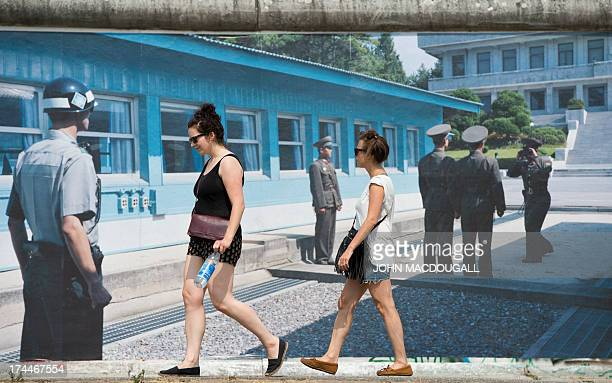 Visitors walk past a giant photograph showing the Demilitarized Zone at Panmunjom at the 'Wall on Wall' exhibition by German photographer Kai...