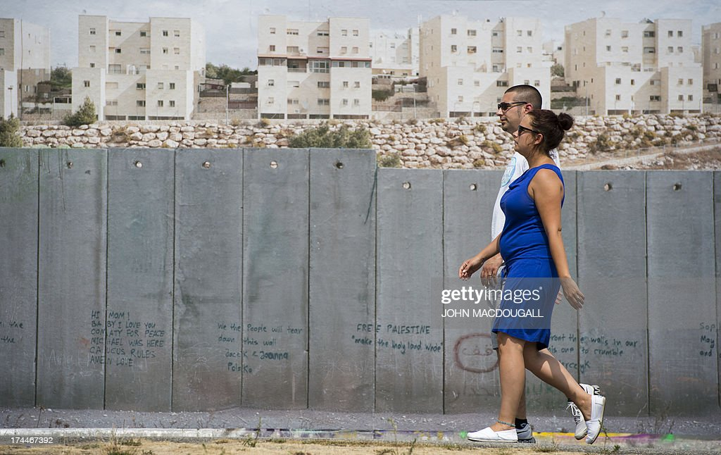 Visitors walk past a giant photograph showing the 'security barrier' at the West Bank (Israel-Palestine) at the 'Wall on Wall' exhibition by German photographer Kai Wiedenhoefer, displayed on a remaining section of the Berlin wall July 26, 2013. Wiedenhoefer's 'Wall on Wall' project features giant panoramic photographs of walls taken in Northern Ireland, Iraq, Cyprus, the West Bank, Morocco, South Korea and the border between the United States and Mexico. The exhibition takes place between10 July and 13 September 2013. AFP PHOTO / JOHN MACDOUGALL