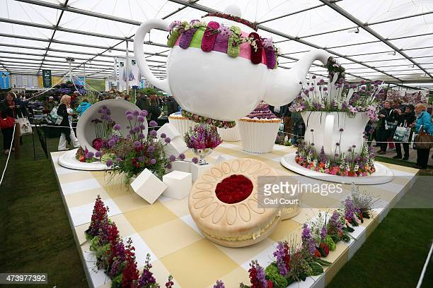 Visitors walk past a giant teapot on display on the first public day of the Chelsea Flower Show on May 19 2015 in London England The show which has...