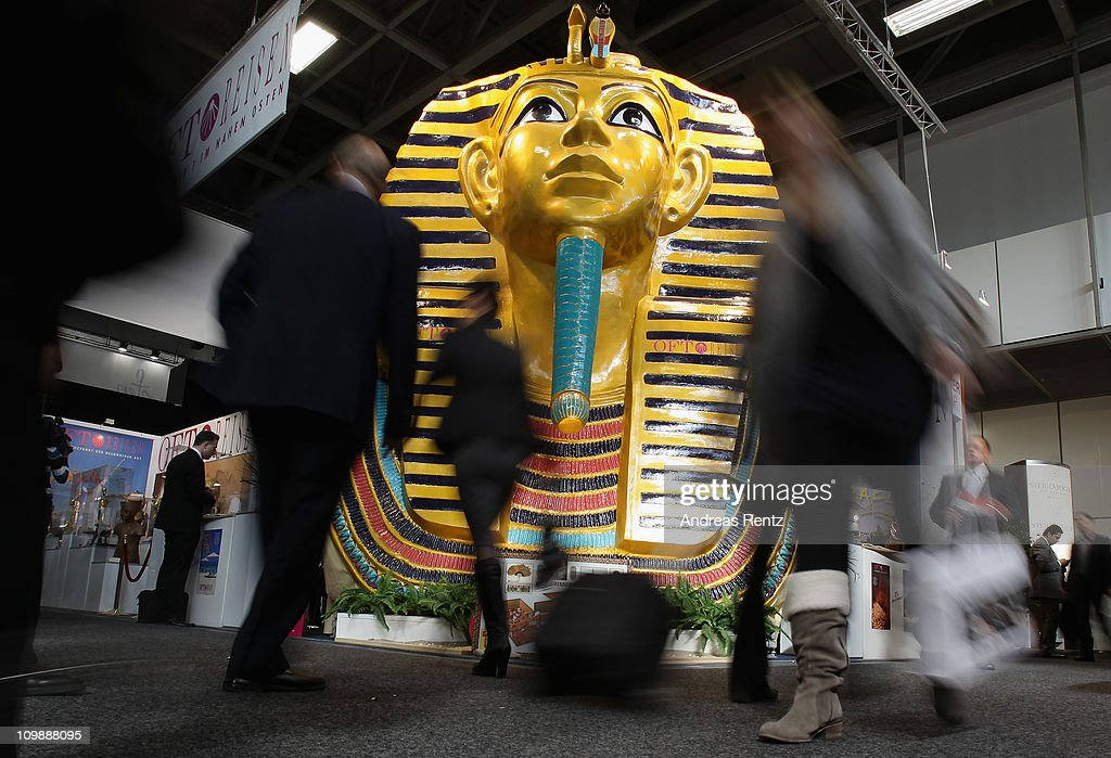 Visitors walk past a giant Tutankhamun mask at the Egypt pavillion at the ITB International tourism trade fair on March 9 2011 in Berlin Germany The...