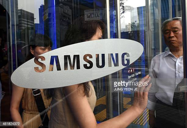 Visitors walk past a glass door showing the logo of Samsung Electronics at the company's showroom in Seoul on July 8 2014 Samsung estimated that its...