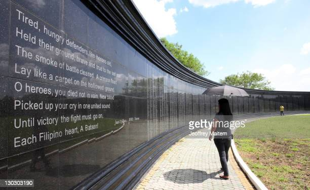 Visitors walk past a memorial wall inscribed with names of Filipino and US soldiers who died as prisoners of war from the Bataan Death March during...