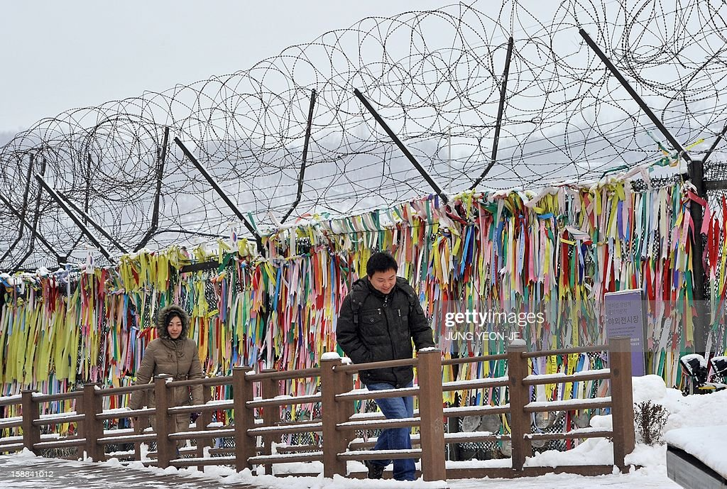 Visitors walk past a military barbed wire fence covered with hanging 'reunification ribbons' at Imjingak peace park in Paju near the Demilitarized Zone (DMZ) dividing the two Koreas on January 1, 2013. North Korean leader Kim Jong-Un called on January 1, 2013 for an easing of tensions with the South and flagged a 'radical turnabout' in the national economy in a rare voiced message broadcast on state television.