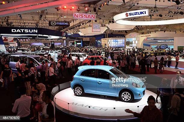 Visitors walk past a Nissan Motor Co March subcompact vehicle front standing on display at the Gaikindo Indonesia International Auto Show in Jakarta...
