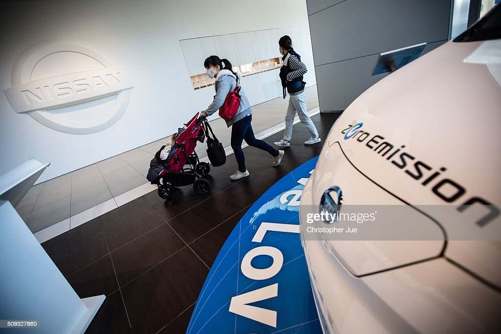Visitors walk past a Nissan zero emission vehicle displayed at the company's showroom on February 10, 2016 in Tokyo, Japan. Nissan Motor Co., Ltd., announced the financial results for the third quarter of fiscal year 2015 ending March 31, 2016. The net revenues resulted in 8.9430 trillion yen, the operating profit, 587.5 billion yen, and the net income 452.8 billion yen, For the April-December 2015 period, Nissan sold a total of 3,891,000 vehicles globally.