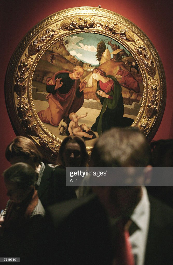 Visitors walk past a painting which is p