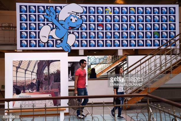 Visitors walk past a panel exhibiting characters from the Belgian comic series 'The Smurfs' created by Belgian cartoonist Peyo and a plate from the...