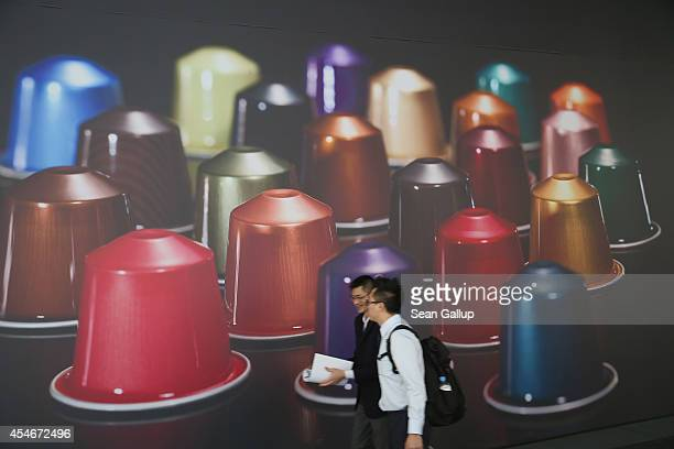 Visitors walk past a picture of espresso coffee capsules at the Nespresso stand at the 2014 IFA home electronics and appliances trade fair on...