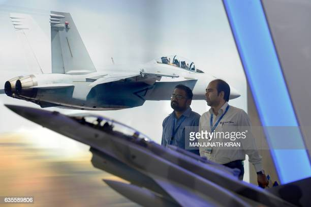 Visitors walk past a poster at a stall in the exhibition area on the third day of the 11th edition of 'Aero India' a biennial international aerospace...
