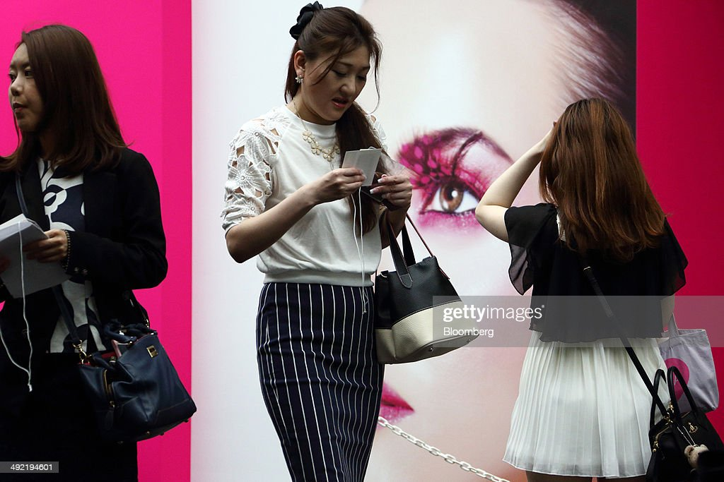 Visitors walk past a poster for the Beautyworld Japan fair in Tokyo, Japan, on Monday, May 19, 2014. The business-to-business trade fair hosted by Messe Frankfurt is held through May 21. Photographer: Tomohiro Ohsumi/Bloomberg via Getty Images