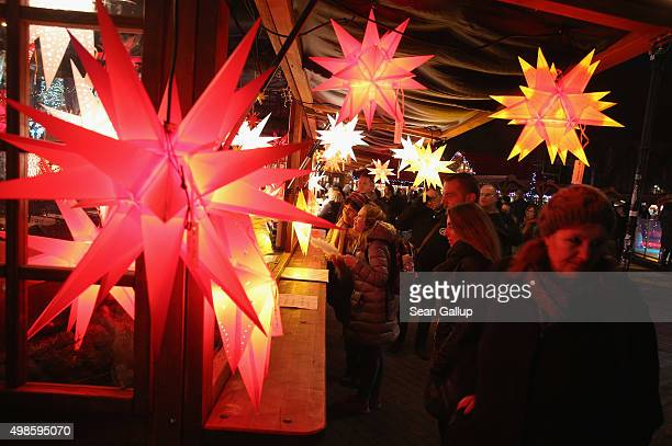 Visitors walk past a stall selling illuminated stars at the annual Christmas market at Alexanderplatz on November 24 2015 in Berlin Germany Christmas...