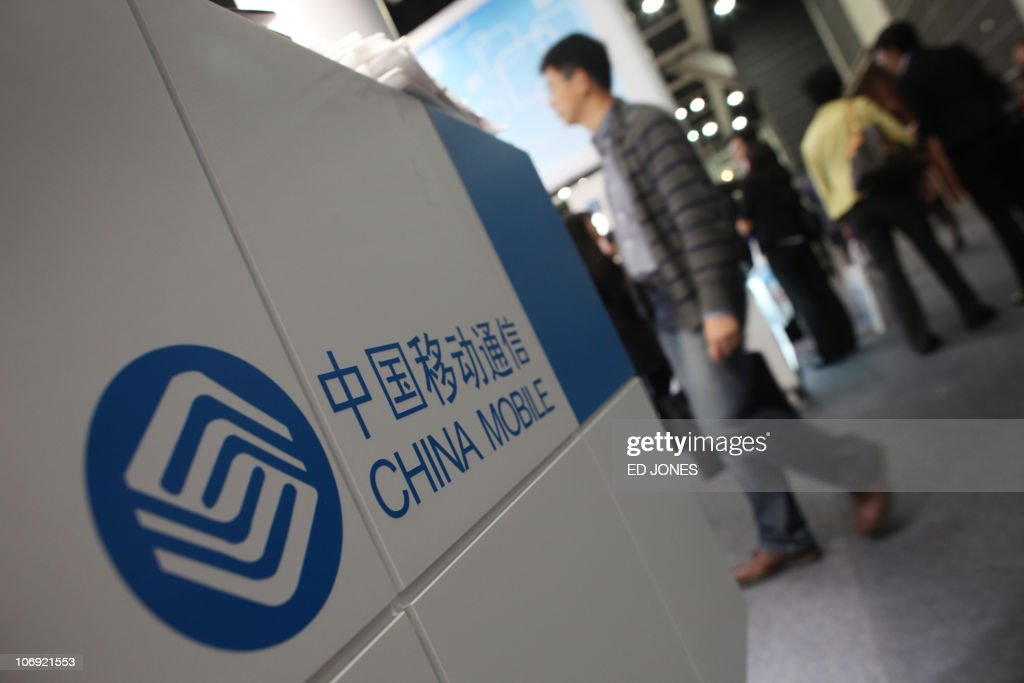 Visitors walk past a stand for China Mobile, the world's largest mobile phone operator, at the Mobile Asia Congress in Hong Kong on November 17, 2010. The annual gathering of industry leaders features discussions and meetings aimed at advancing the mobile communications business.