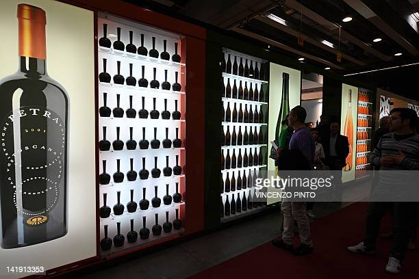 Visitors walk past a stand of Toscan Petra wine on March 25 2012 at the Vinitaly exposition in Verona The 46th international wine and spirits...