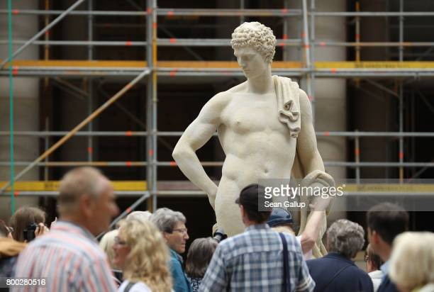 Visitors walk past a statue in the Schlueterhof courtyard during open house day at the construction site of the Berlin City Palace which will house...