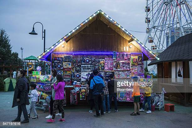 Visitors walk past a toy stall at the National Amusement Park known as the Children's Park in Ulaanbaatar Mongolia on Wednesday July 13 2016 The...