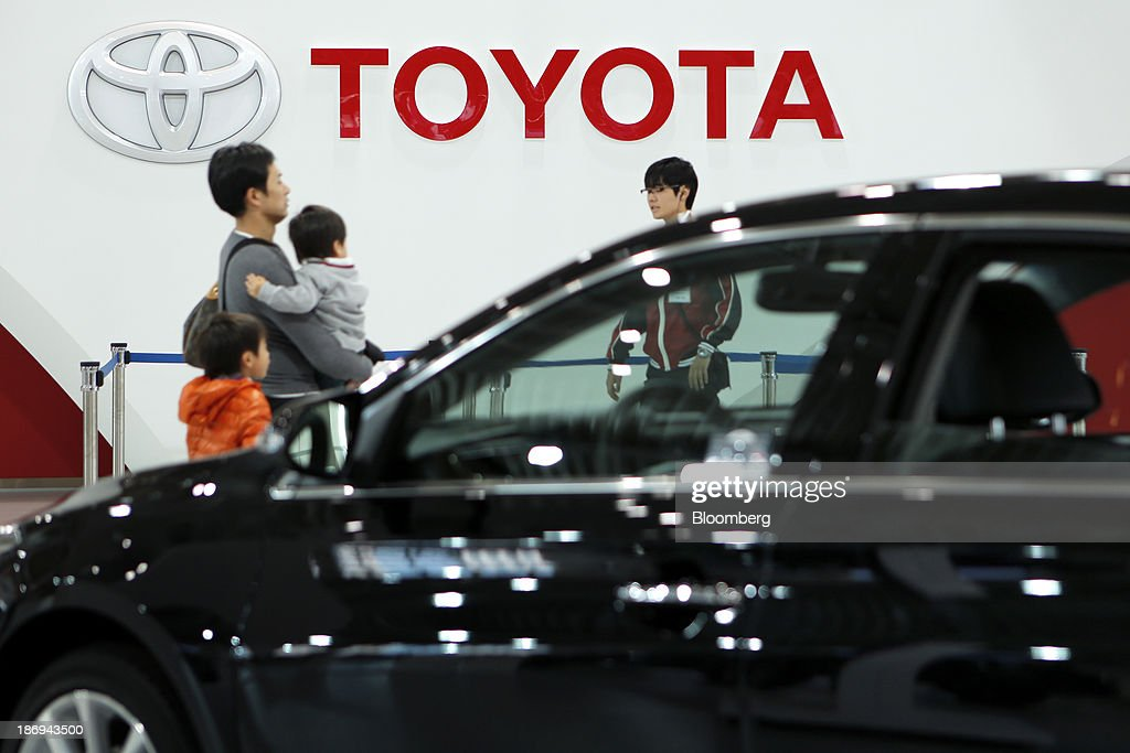 Visitors walk past a Toyota Motor Corp. Avalon vehicle, front, at the company's showroom in Tokyo, Japan, on Tuesday, Nov. 5, 2013. Toyota, the world's largest automaker, will probably deliver record semiannual profit when it reports earnings tomorrow, as the weaker yen bolsters the value of Japanese cars sold overseas. Photographer: Kiyoshi Ota/Bloomberg via Getty Images