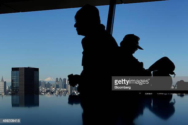 Visitors walk past a view of the city skyline seen from an observation deck in Tokyo Japan on Tuesday Dec 24 2013 Japan unveiled a record budget for...