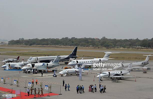 Visitors walk past aircraft parked on display at Begumpet Airport for the India Aviation 2014 airshow in Hyderabad on March 12 2014 The fourth...