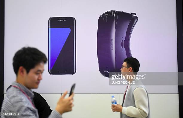 Visitors walk past an advertisement for Samsung Electronics' Galaxy S7 Edge and Gear VR during the Korea Electronics Grand Fair at an exhibition hall...