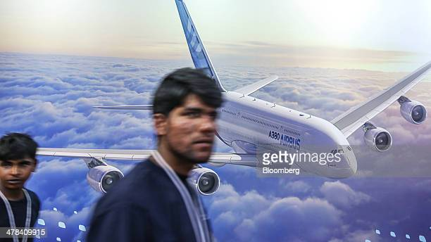 Visitors walk past an advertisement for the Airbus SAS A380 aircraft at the company's pavilion at the India Aviation 2014 air show held at the...
