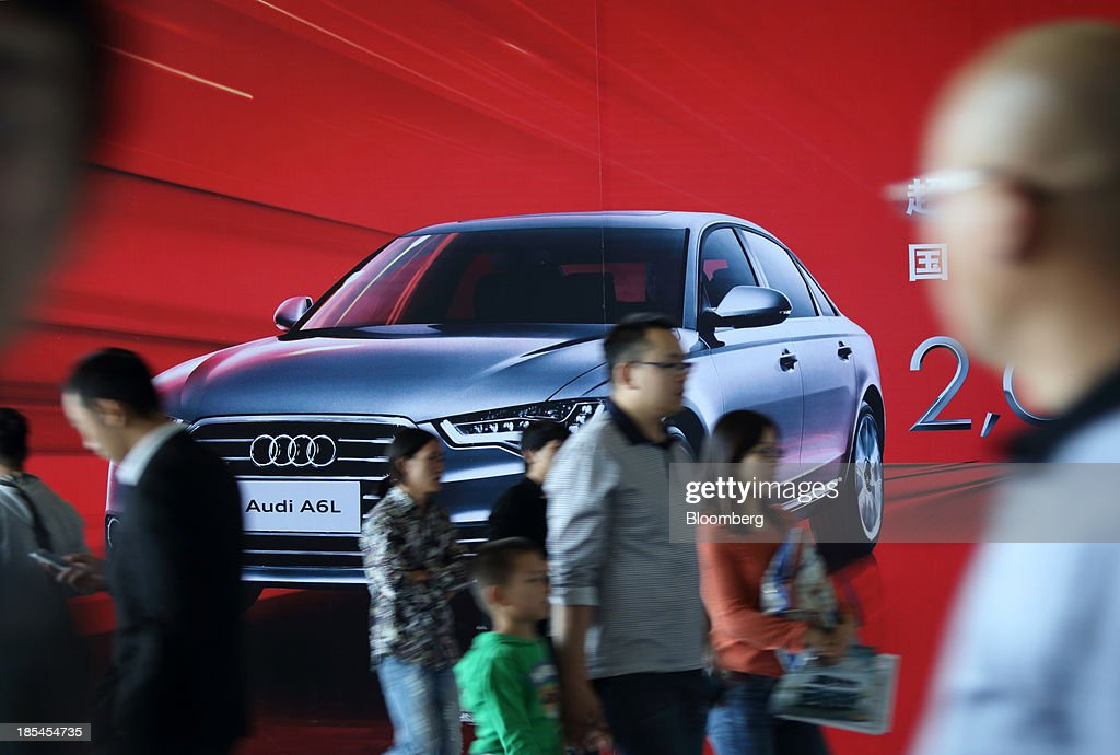 Visitors walk past an advertisement for the Audi A6L sedan manufactured by FAW Audi, the joint venture between Audi AG, Volkswagen AG, and FAW Group Corp., at the Wuhan Motor Show 2013 in Wuhan, China, on Saturday, Oct. 19, 2013. The show will be held through Oct. 23. Photographer: Tomohiro Ohsumi/Bloomberg via Getty Images