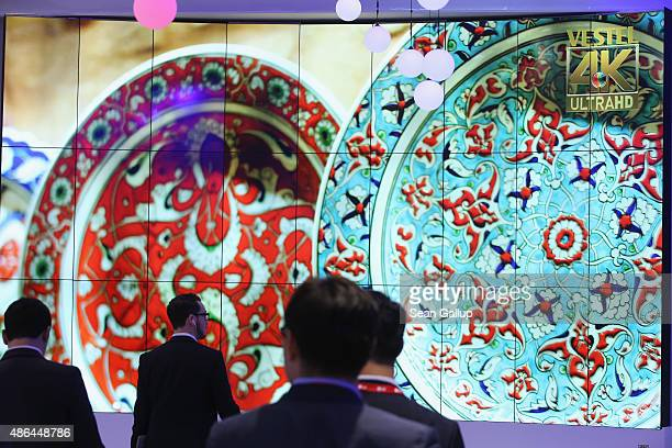 Visitors walk past an array of 4K UltraHD television monitors at the Vestel stand at the 2015 IFA consumer electronics and appliances trade fair on...