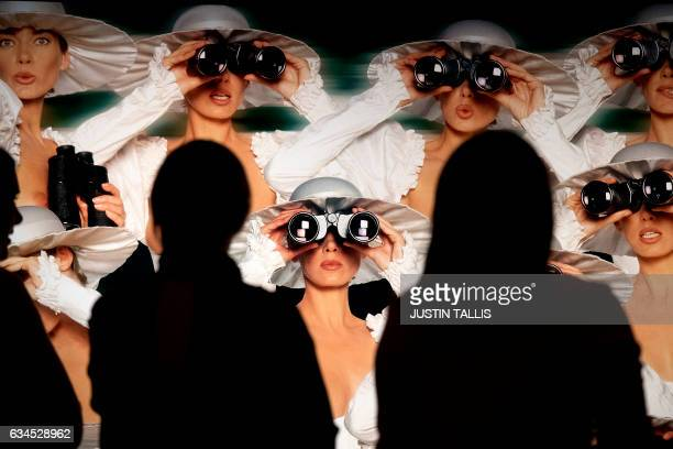 Visitors walk past an artwork entitled 'Ascot' 1995 by German photographer Gunter Sachs with an estimated price of 800012000 GBP during a photocall...