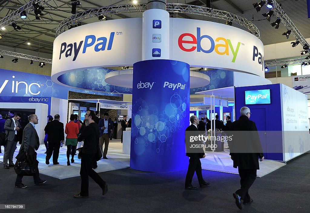 Visitors walk past an Ebay and PayPal stand at the 2013 Mobile World Congress in Barcelona on February 27, 2013. The 2013 Mobile World Congress, the world's biggest mobile fair, is held from February 25 to 28 in Barcelona. AFP PHOTO / JOSEP LAGO