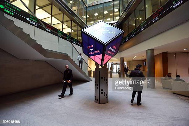 Visitors walk past an illuminated rotating cube displaying share price information for the London Stock Exchange as it stands in the atrium of the...