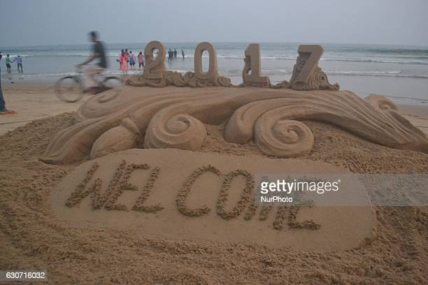 Visitors walk past behind the New Year sand sculpture creating by sand artist Sudarshan Pattnaik for visitors attraction on the eve of New Year at...