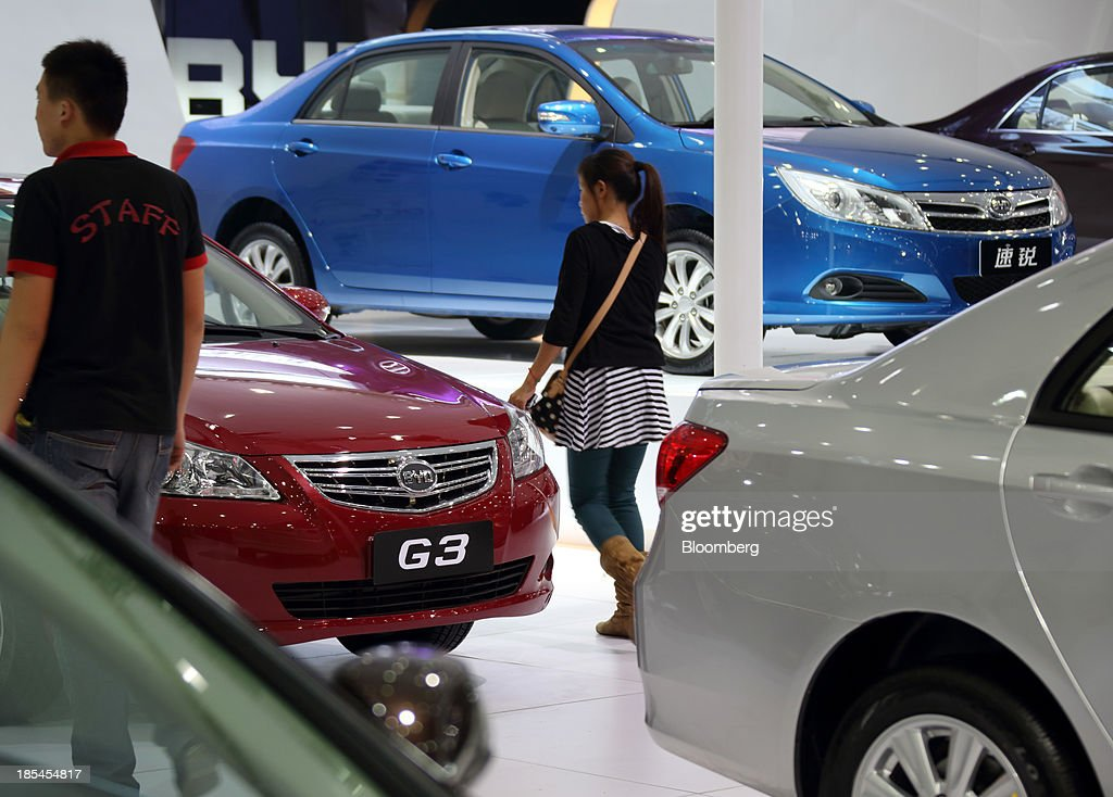 Visitors walk past BYD Co. vehicles displayed at the company's booth at the Wuhan Motor Show 2013 in Wuhan, China, on Saturday, Oct. 19, 2013. The show will be held through Oct. 23. Photographer: Tomohiro Ohsumi/Bloomberg via Getty Images