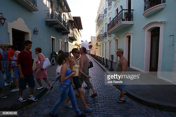 Visitors walk past colorful homes that line the cobblestoned streets April 25 2004 in Old San Juan the original capital city of San Juan Puerto Rico...