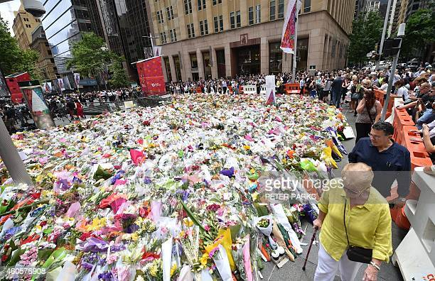 Visitors walk past flowers at a makeshift memorial near the scene of a fatal siege in the heart of Sydney's financial district on December 17 2014...