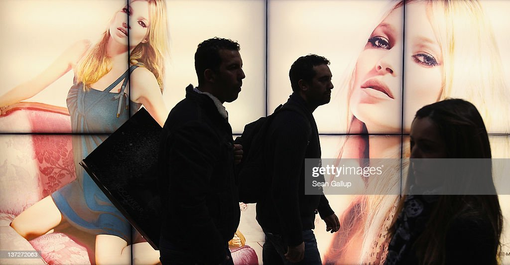Visitors walk past illumianted photographs at the Liu-Jo stand at the 2012 Winter Bread And Butter fashion trade fair at former Tempelhof Airport on January 18, 2012 in Berlin, Germany. Bread And Butter is a semi-annual event and is among Europe's major fashion trade fairs.