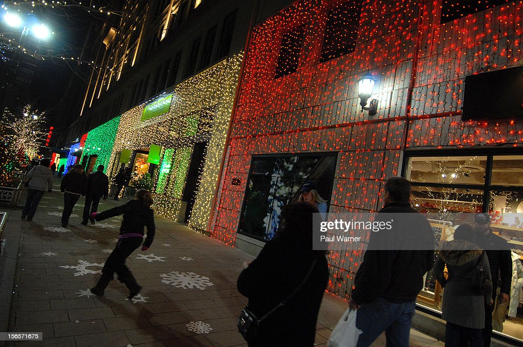 Visitors walk past lighted store fronts on Woodward Ave during the City of Detroit's Christmas Tree Lighting celebration at Campus Martius Park on November 16, 2012 in Detroit, Michigan.