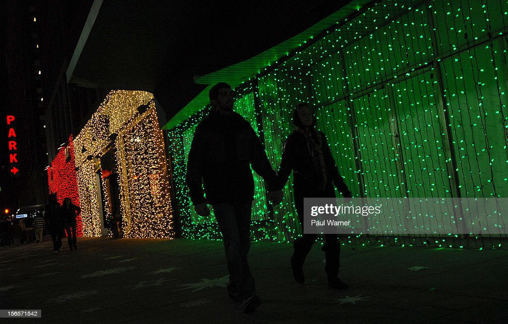 Visitors walk past lighted storefronts on Woodward Ave during the City of Detroit's Christmas Tree Lighting celebration at Campus Martius Park on November 16, 2012 in Detroit, Michigan.