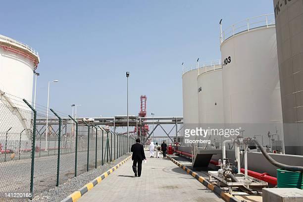 Visitors walk past oil tanks inside Fujairah port in Fujairah United Arab Emirates on Monday March 12 2012 ENOC as Dubai's governmentowned refiner is...