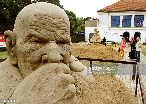 Visitors walk past sand sculptures on display at the International sand sculptures festival in Palanga Lithuania on July 2014 AFP PHOTO / PETRAS...