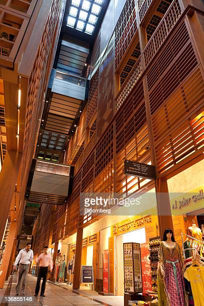 Visitors walk past stores in the Central Market souk an Aldar PJSC project designed by architects Foster and Partners Ltd in Abu Dhabi United Arab...