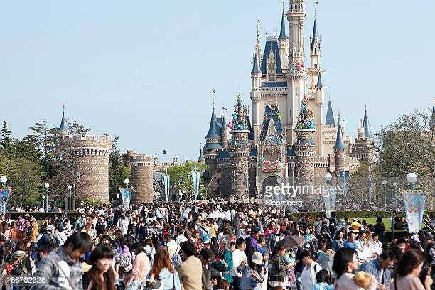 Visitors walk past the Cinderella Castle during 30th anniversary celebrations of Tokyo Disneyland operated by Oriental Land Co at the amusement park...