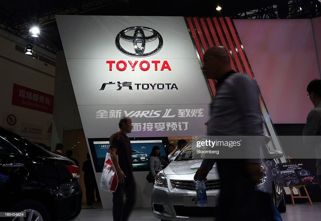 Visitors walk past the GAC Toyota Motor Co. booth at the Wuhan Motor Show 2013 in Wuhan, China, on Saturday, Oct. 19, 2013. The show will be held through Oct. 23. Photographer: Tomohiro Ohsumi/Bloomberg via Getty Images