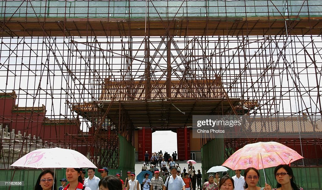 Visitors walk past the Hall of Supreme Harmony surrounded by scaffolding and netting at the centre of the Forbidden City on June 9, 2006 in Beijing, China. Repairs on the Hall of Supreme Harmony (Taihedian in Chinese) in the Forbidden City began in January. They are expected to be completed by 2008, in time for the Beijing Olympic Games. As the symbol of imperial power, the hall was where Ming and Qing (1368-1911) emperors received high officials and exercised their rule over the nation.