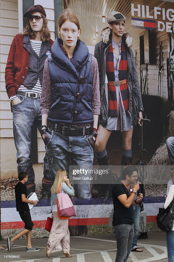 Visitors walk past the Hilifiger Denim stand at the 2012 Bread & Butter fashion trade fair at former Tempelhof Airport on July 6, 2012 in Berlin, Germany. Bread & Butter is the world's largest trade fair for street fashion.