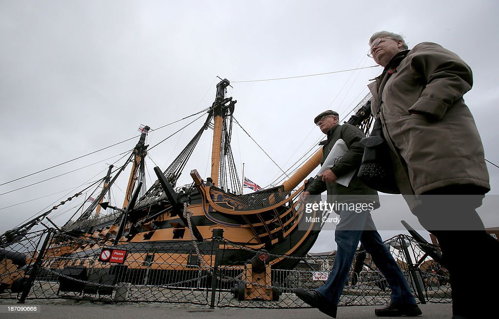 Visitors walk past the historic ship HMS Victory displayed in the Historic Dockyard besides the BAE systems yard at the HM Naval Base in Portsmouth dockyard following the announcement that the company will be cutting jobs on November 6, 2013 in Portsmouth, England. The cuts are being made following a decline in orders, with 1775 jobs going between the yards in Scotland and England with the end of shipbuilding altogether at the Portsmouth yard.