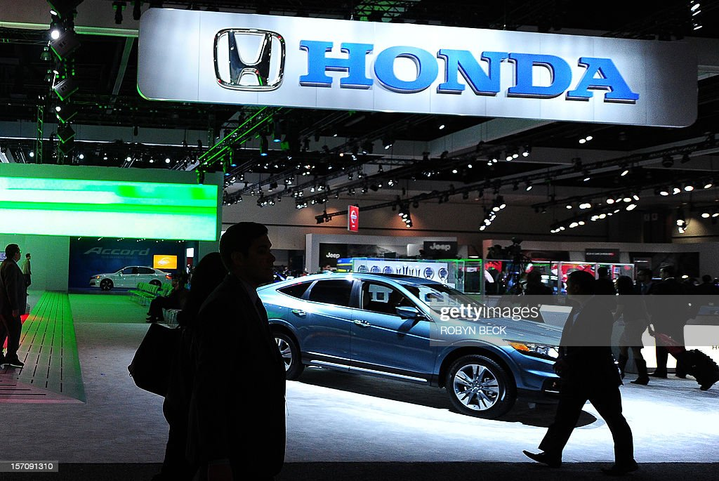Visitors walk past the Honda display at the 2012 Los Angeles Auto Show in Los Angeles California on media preview day November 28 2012 The LA Auto...
