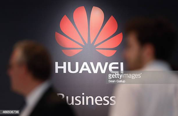 Visitors walk past the Huawei stand at the 2015 CeBIT technology trade fair on March 16 2015 in Hanover Germany China is this year's CeBIT partner...