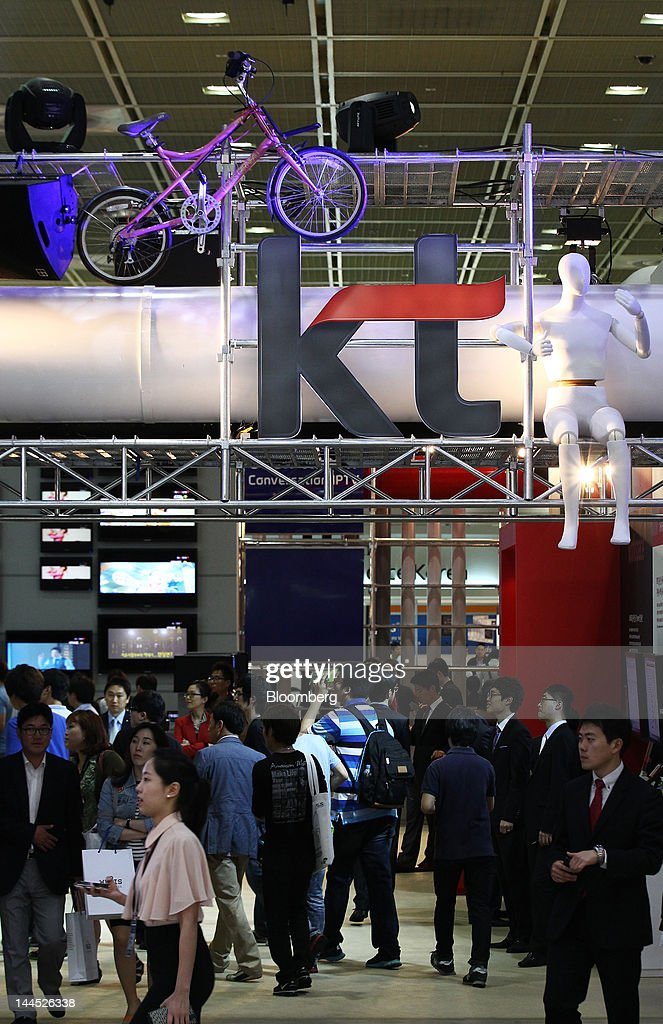 Visitors walk past the KT Corp. booth at the World IT Show 2012 in Seoul, South Korea, on Tuesday, May 15, 2012. The show will be held through May 18. Photographer: SeongJoon Cho/Bloomberg via Getty Images